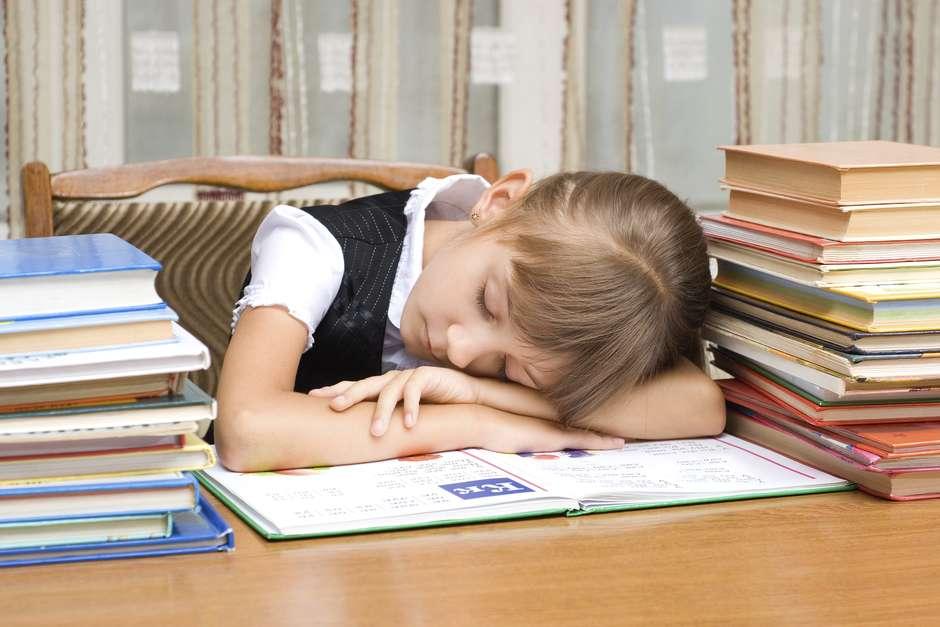 The tired schoolgirl has fallen asleep during reading